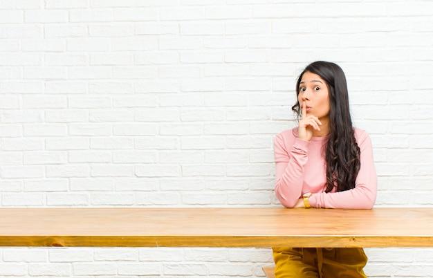 Junge hübsche lateinische frau, die um ruhe und stille bittet, mit dem finger vor mund gestikuliert, shh sagt oder ein geheimes sitzen vor einer tabelle hält