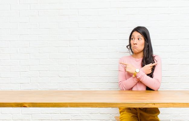 Junge hübsche lateinische frau, die verwirrt und verwirrt, unsicher schaut und in entgegengesetzte richtungen mit den zweifeln sitzen vor einer tabelle zeigt