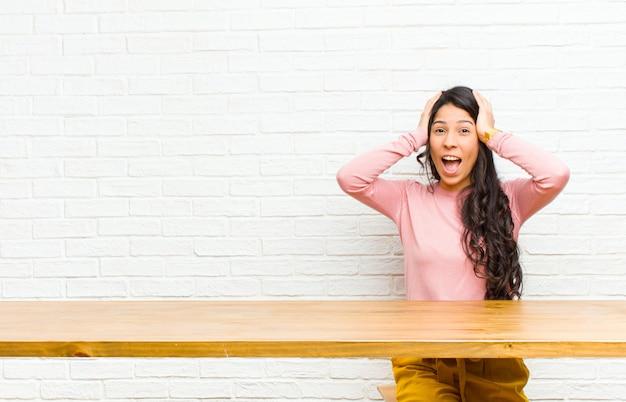 Junge hübsche lateinische frau, welche die hände zum kopf anhebt, mit offenem mund, das gefühl extrem glücklich, überrascht, aufgeregt und glücklich, vor einem tisch sitzend