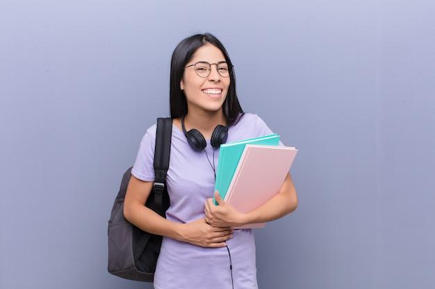 Junge hübsche lateinische studentin gegen graue wand