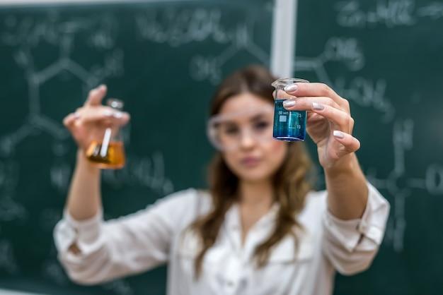 Junge hübsche lehrerin hält die flasche mit der farbflüssigkeit in der nähe der tafel bei einer chemiestunde im unterricht.