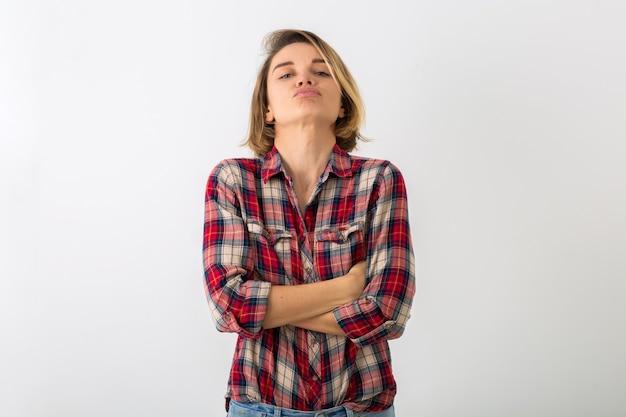 Junge hübsche lustige emotionale frau im karierten hemd, das lokalisiert auf weißer studiowand aufwirft, die verärgerte geste zeigt