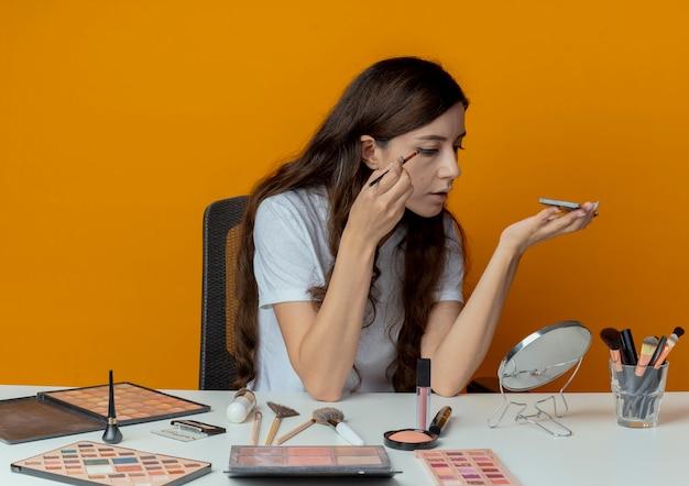 Junge hübsche mädchen sitzen am schminktisch mit make-up-tools, die auf den spiegel schauen und lidschatten auftragen