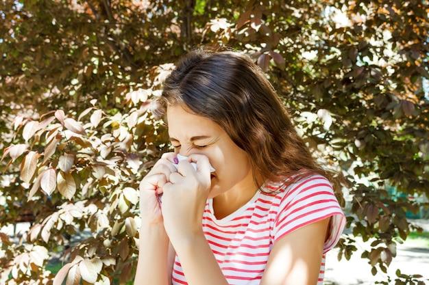 Junge hübsche mädchenschlagnase vor baum. frühlingsallergie-konzept