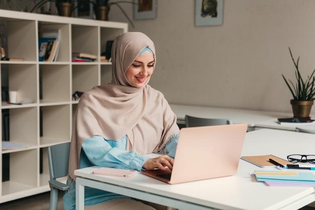 Junge hübsche moderne muslimische frau im hijab, die am laptop im büroraum arbeitet, bildung online