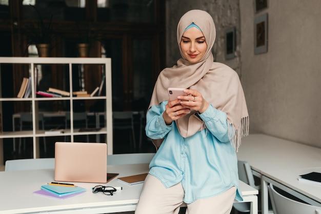 Junge hübsche moderne muslimische frau im hijab, die im büroraum arbeitet, bildung online