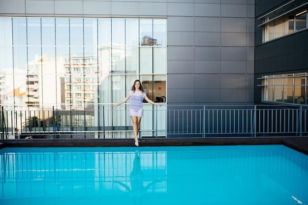 Junge hübsche modesportfrau, die im sommer im freien in heißem wetter im bikini auf pool aufwirft