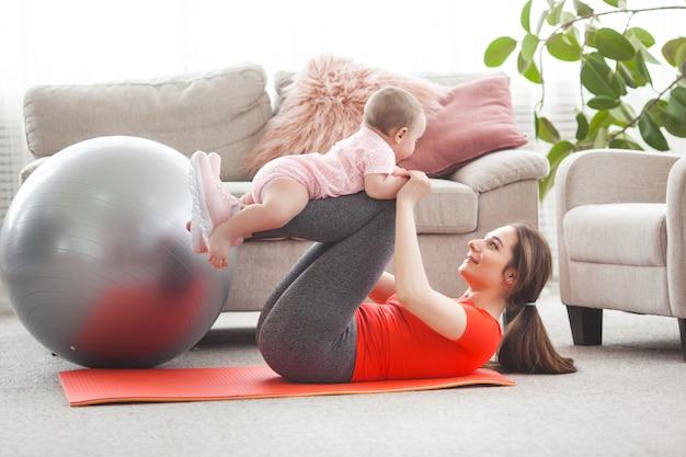 Junge hübsche mutter, die mit ihrem kleinen kind zu hause trainiert