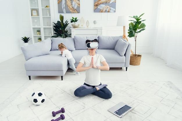 Junge hübsche mutter meditiert in lotus yoga position mit virtual-reality-brille, während ihre tochter cartoons zu hause auf hintergrund sieht. draufsicht.