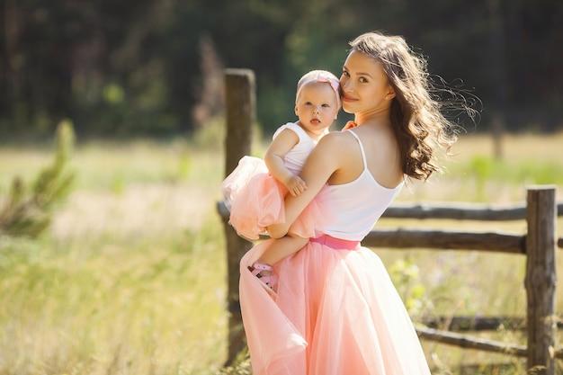 Junge hübsche mutter mit ihrem kleinen baby im freien. schöne frau mit ihrer tochter auf der natur. kleinkind mit ihren eltern