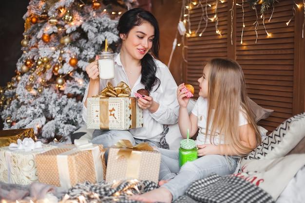 Junge hübsche mutter und ihre kleine tochter teilen weihnachtsgeschenke