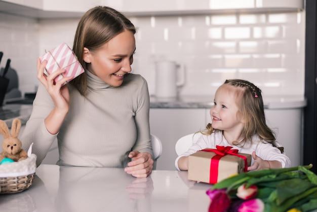 Junge hübsche mutter und tochter mit geschenkbox in der küche