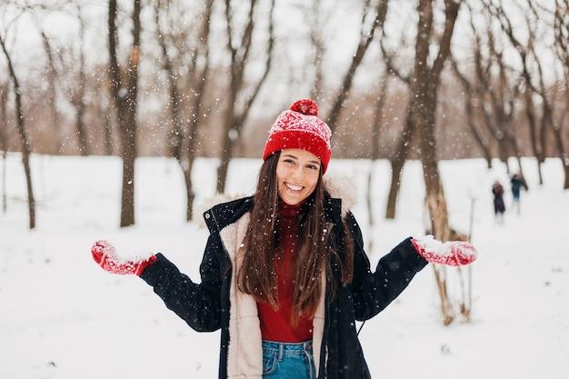 Junge hübsche offen lächelnde glückliche frau in den roten handschuhen und im hut, die schwarzen mantel tragen, der im park im schnee in der warmen kleidung spielt und spaß hat
