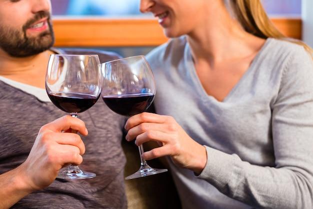 Junge hübsche paare, die zu hause rotwein trinken