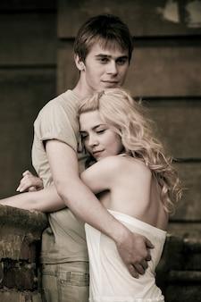 Junge hübsche paare mann und frau sitzen auf einem stein am bordstein. konzert der romantischen beziehung und liebe. schwarzweiss-foto