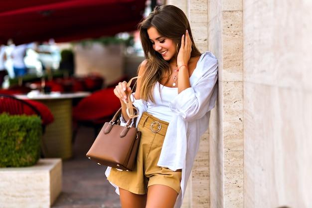Junge hübsche prächtige schüchterne brünette junge frau, die auf pariser straße, eleganter dameblick, sommerzeit, beige farben, reiseerfahrung aufwirft.