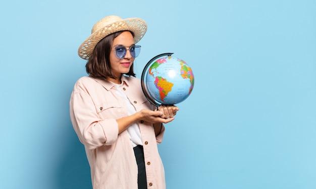 Junge hübsche reisende frau mit einer weltkugelkarte. reise- oder urlaubskonzept