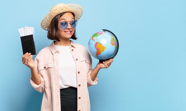 Junge hübsche reisende frau mit einer weltkugelkarte