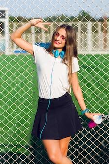 Junge hübsche reizende hipsterfrau, die mit der tasse des gesunden safts aufwirft, lieblingsmusik hört