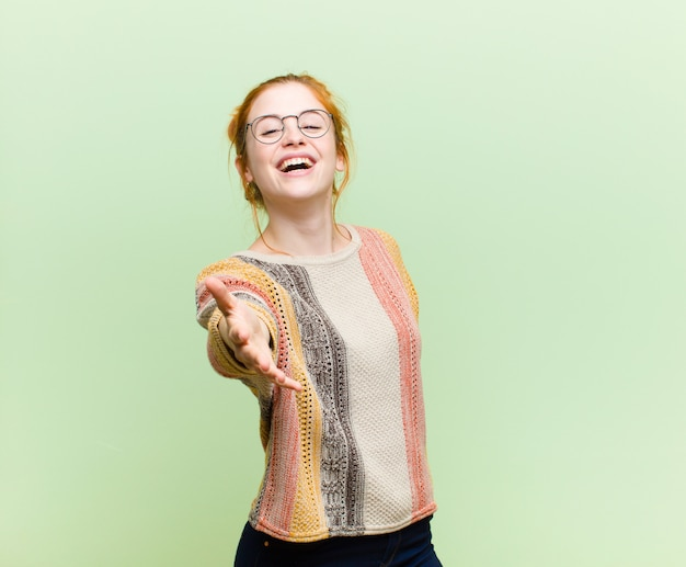 Junge hübsche rothaarige frau lächelnd, glücklich, selbstbewusst und freundlich aussehend, einen handschlag anbietend, um einen deal abzuschließen, kooperierend gegen grüne wand