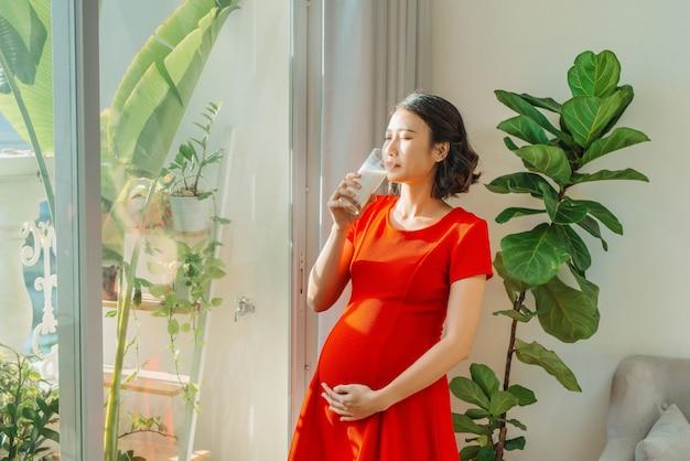 Junge hübsche schwangere frau, die milch trinkt, wenn sie hinter dem fenster steht