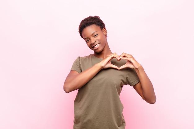 Junge hübsche schwarze frau lächelnd, die herzform mit beiden händen gegen rosa wand macht