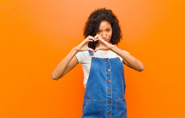 Junge hübsche schwarze frau lächelt und fühlt sich glücklich, süß, romantisch und verliebt, herzform mit beiden händen gegen orange wand machend