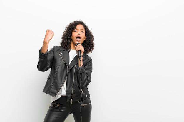 Junge hübsche schwarze frau mit einem mikrofon, das eine lederjacke trägt