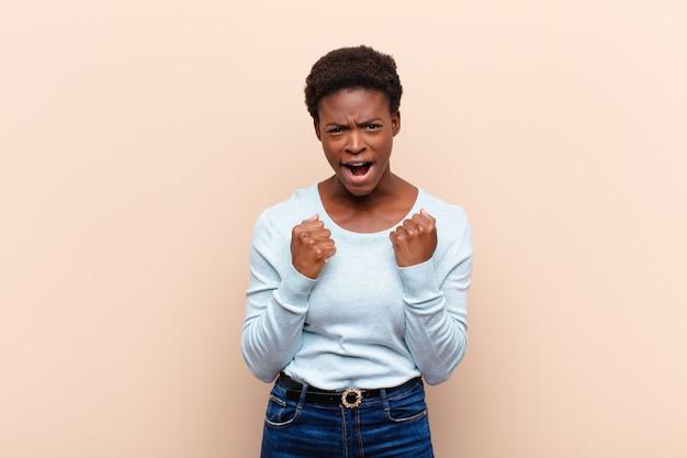 Junge hübsche schwarze frauen schreien aggressiv mit genervtem, frustriertem, wütendem blick und engen fäusten und fühlen sich wütend