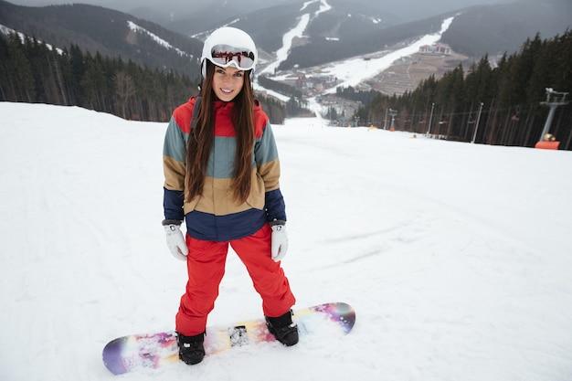 Junge hübsche snowboarderin auf den pisten frostigen wintertag