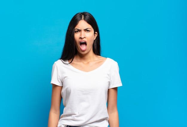 Junge hübsche spanische frau, die aggressiv schreit, sehr wütend, frustriert, empört oder genervt aussieht und nein schreit