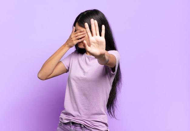 Junge hübsche spanische frau, die gesicht mit hand bedeckt und andere hand nach vorne legt, um kamera zu stoppen, fotos oder bilder ablehnend