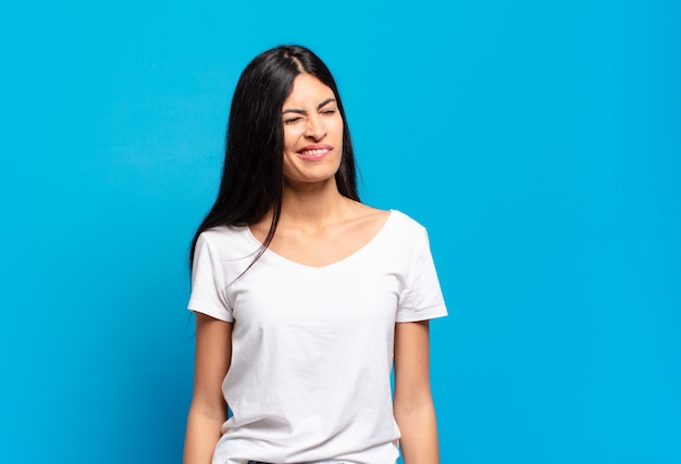 Junge hübsche spanische frau, die glücklich und freundlich schaut, lächelt und ihnen mit einer positiven einstellung ein auge zuzwinkert