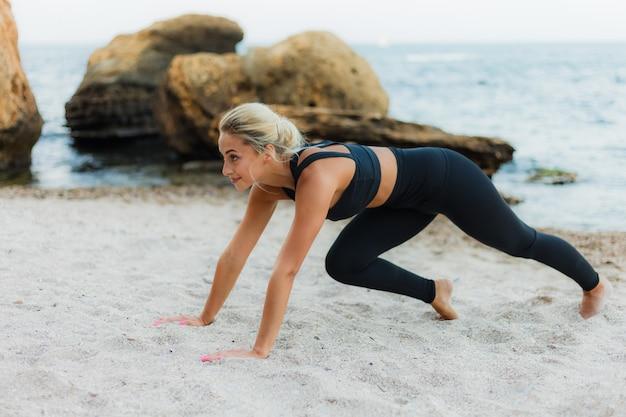 Junge hübsche sportblonde frau in der sportbekleidung übt eine übungsplanke auf dem sand am wilden strand. training im freien