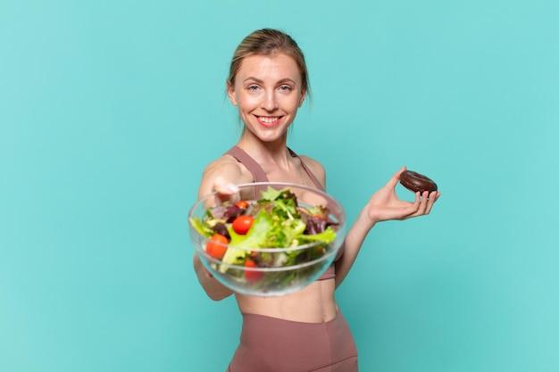 Junge hübsche sportfrau glückliche ausdruckshand, die ein sandwich und einen donut hält