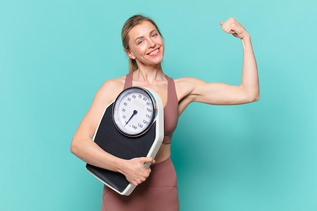 Junge hübsche sportfrau glücklicher ausdruck und hält eine waage weight