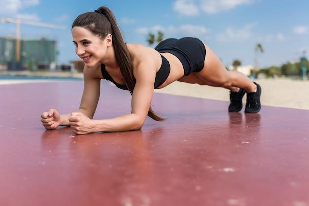 Junge hübsche sportfrau in sportbekleidung übt eine übungsplanke am strand.