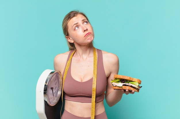 Junge hübsche sportfrau zweifelt oder unsicherer ausdruck und hält eine waage und ein sandwich