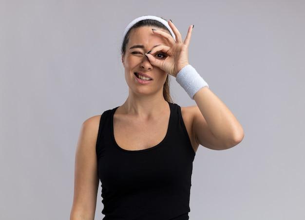 Junge hübsche sportliche frau mit stirnband und armbändern, die blickgeste macht