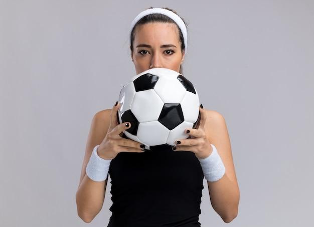 Junge hübsche sportliche mädchen mit stirnband und armbändern, die fußball von hinten halten