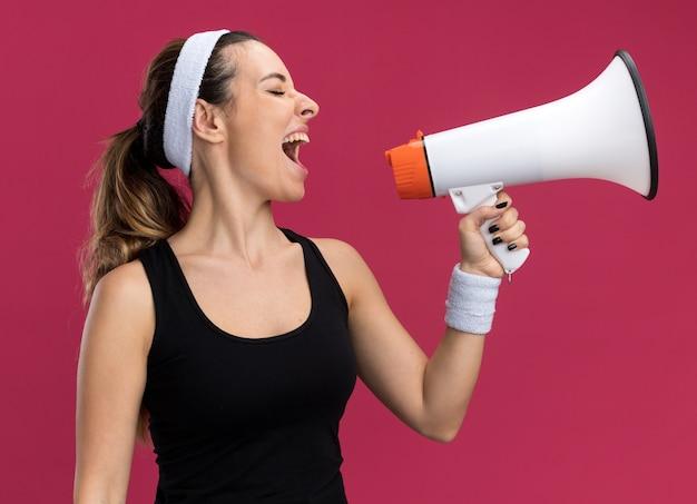 Junge hübsche sportliche mädchen mit stirnband und armbändern, die kopf zur seite drehen und im lautsprecher mit geschlossenen augen schreien