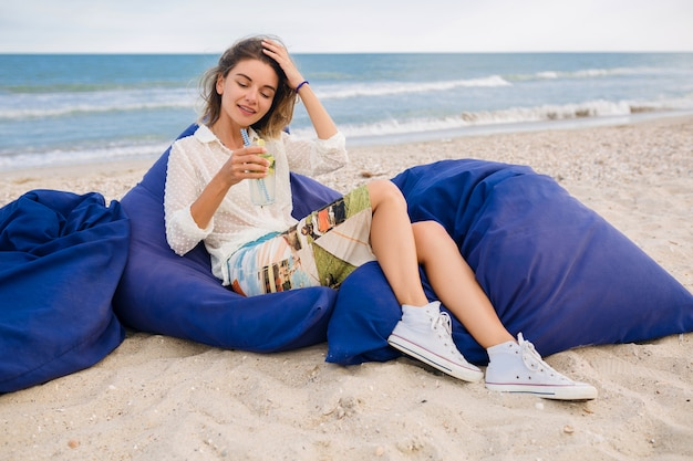 Junge hübsche stilvolle frau, die in sitzsäcken am strand sitzt und mojito-cocktail trinkt, sommerart-outfit, entspannend, beine in turnschuhen, natürlicher blick