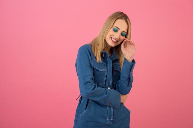 Junge hübsche stilvolle lächelnde denkende flirty suchende frau in rosa pullover und sonnenbrille lokalisiert auf rosa studiohintergrund