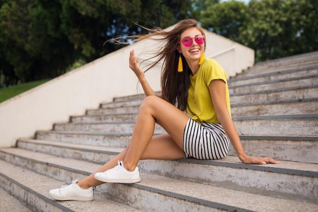 Junge hübsche stilvolle lächelnde frau, die spaß im stadtpark hat und gelbes oberteil, minirock, rosa sonnenbrille, weiße turnschuhe, modetrend im sommerstil, lange beine, auf treppen sitzend, langes haar winkend trägt