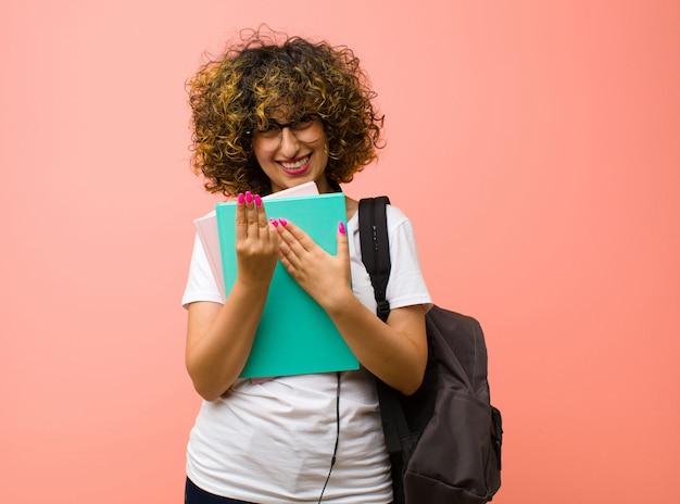 Junge hübsche studentin, die freundlich lächelt und schaut, nummer acht oder acht mit der hand vorwärts zeigend, gegen rosa wand herunterzählend
