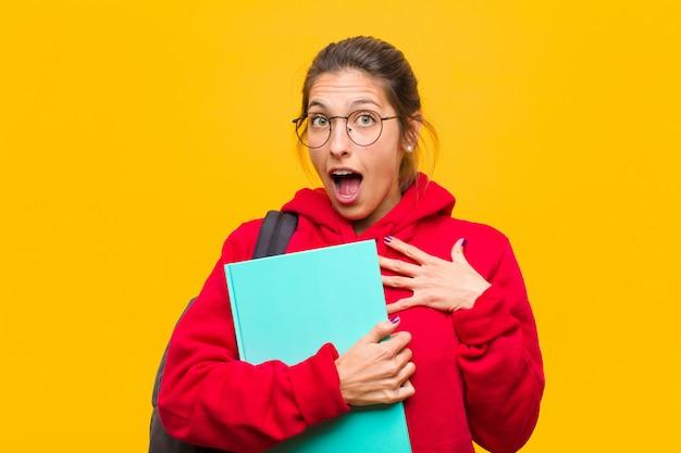 Junge hübsche studentin fühlt sich schockiert, erstaunt und überrascht, mit der hand auf der brust und offenem mund, und sagt wer, ich?