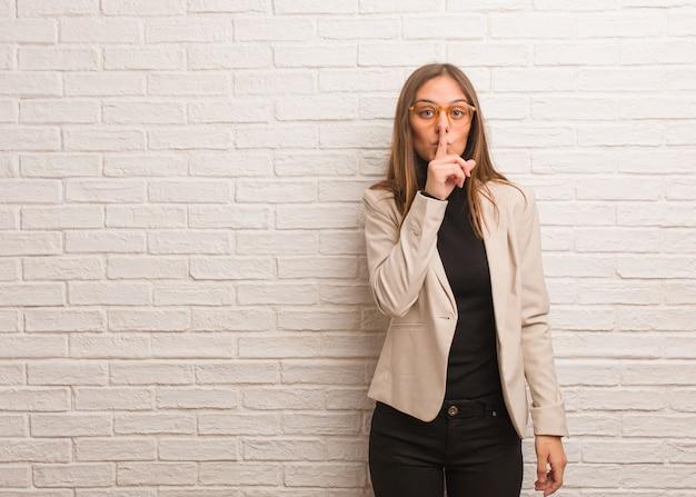 Junge hübsche unternehmerfrau, die ein geheimnis hält oder um ruhe bittet