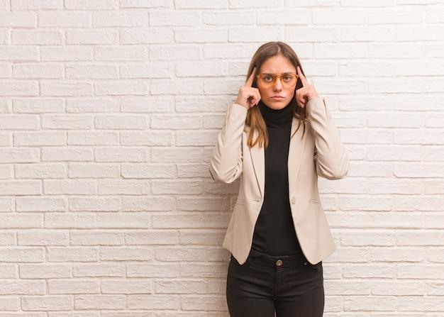 Junge hübsche unternehmerfrau, die eine konzentrationsgeste tut