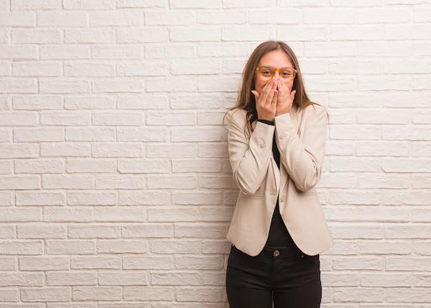 Junge hübsche unternehmerfrau, die über etwas, mund mit den händen bedeckend lacht