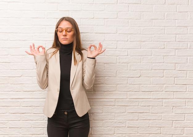 Junge hübsche unternehmerfrau, die yoga durchführt